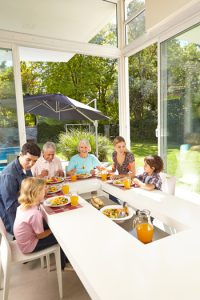 image shows family eating in sunroom on Porch Coversion of Seneca, SC website for sunrooms, screened rooms, EZE Breeze Windows and patio enclosures